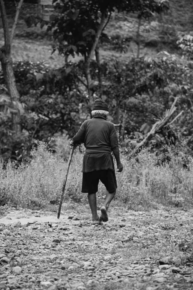 grayscale photography of person holding stick